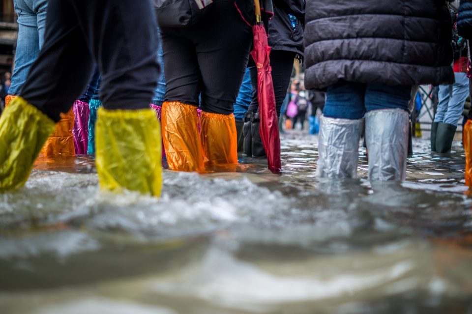 people in rain boots during a flood